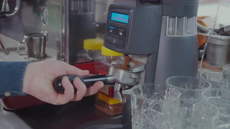 latte macchiato : Male barman is using automatic grinder for coffee. He is holding filter and filling it, then shaking, close-up view in cafe bar
