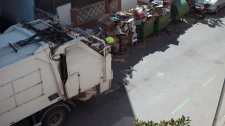 kolektor : Male dustman is removing paper garbage and putting it in garbage truck. Top view from window of house in courtyard in summer morning