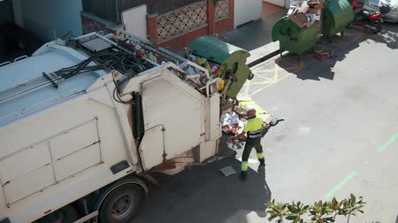 coletor : Refuse truck is lifting garbage container automatically and pouring waste inside. Male worker is standing near and controlling