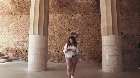 ler : Female traveler is strolling inside ancient spanish castle. She is visiting this landmark, examining booklet with history and map