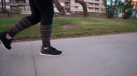 tutmak : Adult sporty woman is doing evening run in town. She is jogging on path in park, close-up of her feet