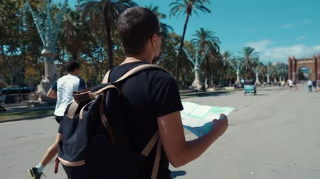 descobrir : Man is holding paper city map of Barcelona and examining it, walking on boulevard in front of Arc de Triomphe. Alone male traveler in Spain