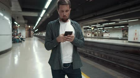 townsman : Handsome adult man with headphones in ears is viewing smartphone in station of underground. He is waiting a train and typing sms