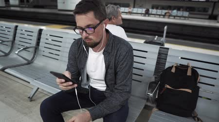 mobile music : Adult townsman is resting on bench in station of underground. He is waiting train and listening to music on smartphone