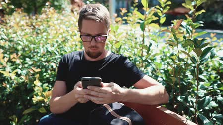 townsman : Townsman is resting in park with mobile phone, using internet. he is sitting on bench in hot sunny day Stock Footage