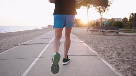 townsman : Male runner is training in sundown time in city embankment. He is jogging, close-up view of his feet from back Stock Footage
