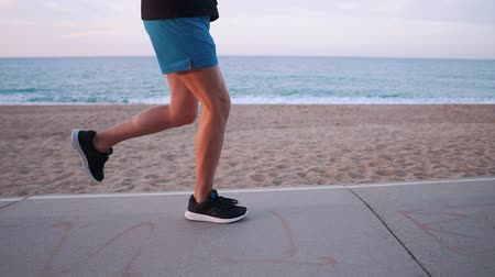 running man : Strong legs of male athlete, close-up view during evening run. Man is jogging near sea coast, healthy lifestyle