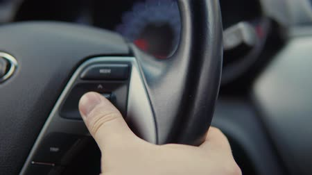 nastavení : Man is sitting inside automobile and controlling onboard computer. He is moving handle on steering wheel and adjusting, close-up
