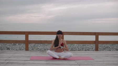 сложены : Calm adult woman is meditating sitting in lotus position on sea coast in morning. She is inhaling and exhaling fresh air and holding folded hands near chest