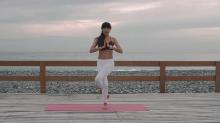 posição : Young pretty woman is performing traditional eagle position in yoga session. She is crossing hands in front of chest, beautiful seascape behind her