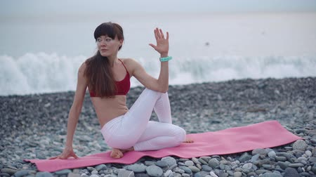 hatha : Gymnast woman is fixing her body twisted, sitting on pebble beach. She is breathing and practicing hatha yoga