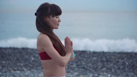dobrado : Adult brunette yogi woman is making meditative practice on seacoast. She is holding folded hands near chest, breathing, waves are crushing in background