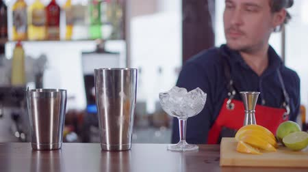 behind bars : Male bartender is mixing drink in bar, standing behind counter. He is using shaker for stirring ingredients, fruits and ice in front of him Stock Footage