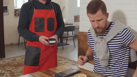 payment terminal : Bearded man is viewing bill in coffee shop and paying by credit card. He is lying it to POS terminal in hands of waiter Stock Footage