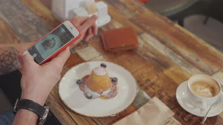 kafeterya : Male visitor of cafeteria is taking picture of his cake in plate. He is holding his mobile phone, focusing and capturing, close-up view Stok Video