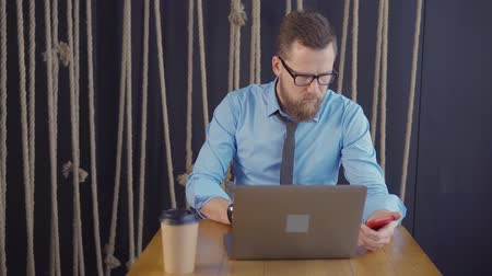 remotely : Male manager is sitting at table in working place, looking on screen of laptop. He is typing and reading messages in smartphone Stock Footage