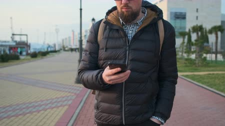 kettyenés : Young man is strolling with mobile phone in hands close-up. He is moving in city area, viewing news in social nets by internet Stock mozgókép