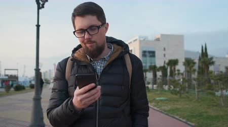 townsman : Young man is walking on pedestrian path in daytime, looking on screen of mobile phone. He is reading messages and news tape and smiling Stock Footage