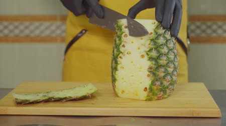 вегетарианство : Close-up shot of a professional cook peeling and slicing pineapple on the wooden board in the kitchen. Cooking exotic meal.