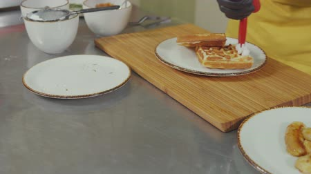 çırpılmış : Close-up of a cook adding whipped cream topping to belgium waffles. Sweet caramel waffles on the plate.
