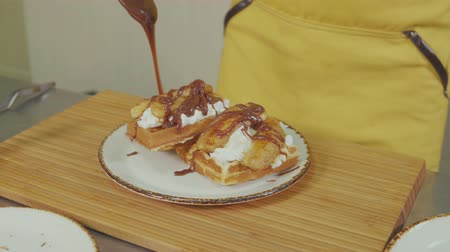 ワッフル : Cook adds caramel topping to waffles with whipped cream, sweet belgium dessert. Delicious looking meal.