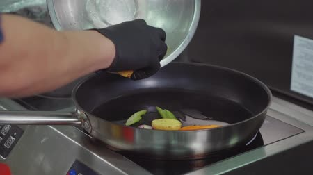 откорме : Close-up shot of restaurant chef putting prepared vegetables from bowl to frying pan on a cooker. Making delicious dish.