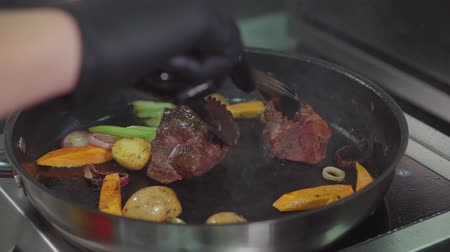 откорме : Close-up of a chefs hands in gloves holding tongs and turning ingredients on frying pan. Tasty meal, high quality dish. Стоковые видеозаписи
