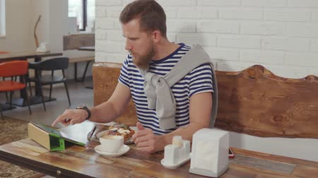 mascarpone : Guy on a break eats beautiful waffles with berries and drinks coffee while reading news on his tablet. Using gadgets while eating. Sweet dessert.
