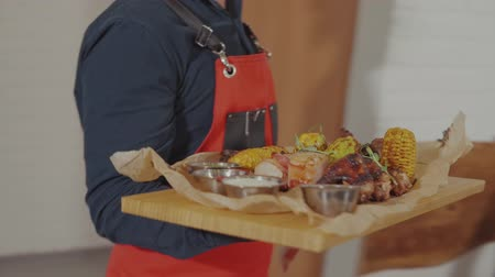 szószok : Waiter serving a big meat meal on wooden board to a client. Man ordered grilled meat with grilled vegetables with four sauces. Big meat plate. Stock mozgókép