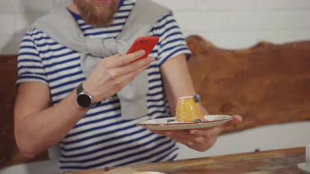 tatlı çörek : Man taking photos of a muffin dessert on a smartphone. Guy holding a plate with blueberry muffin and taking pictures. Stok Video