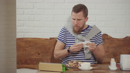 mascarpone : Portrait of a grown man eating waffles for dessert, drinking coffee and sitting online from his tablet, spending lunch time in cafe. Surfing web while eating. Stock Footage