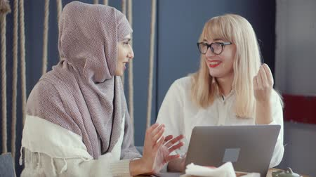 gesticulando : Blonde woman and her muslim female friend are communicating in working room. They are gossiping, talking and gesticulating, laughing cheerfully