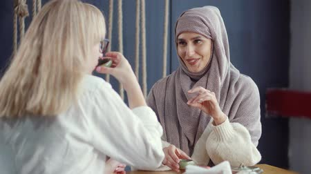 kafeterya : Muslim woman is pouring tea from ceramic teapot in her and her blonde friend cups. Two friends of different ethnic and religious are communicating friendly in cafe