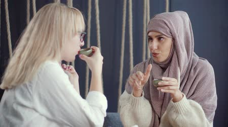 traditie : Moslem woman is communicating cheerfully with adult european woman in cafe. Friends are drinking tea, smiling, laughing and gesticulating