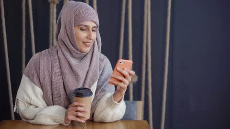 tektura : Smiling arabic woman is looking on screen of her mobile phone. She is sitting in cafeteria, holding cardboard of coffee, typing message