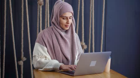 antwoord : Young muslim woman is chatting by internet using notebook with wifi in cafe. She is reading messages and entering answer on keyboard