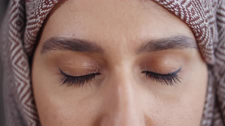 arabeska : Adult muslim woman is opening eyes and looking at camera, close-up view. She is having hijab on head, dark eyes and black arrows on eyelids