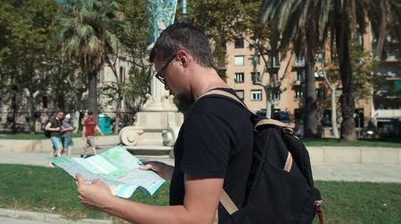 triumphal arch : Close-up of a brunet guy in glasses holding a map of the city, vacation in Europe. Tourist with backpack lost in city, reading map. New in city.