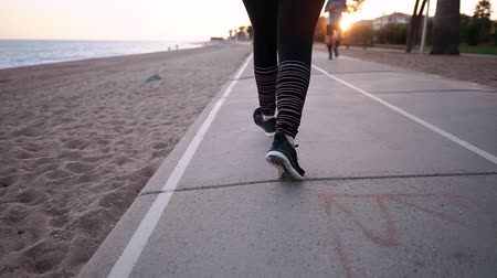 conserva : Close-up shot from behind of a woman running in a black sneakers on a beach, sport activities on a fresh air. Sport concept: woman keeps herself in fit and healthy, beach jogging.