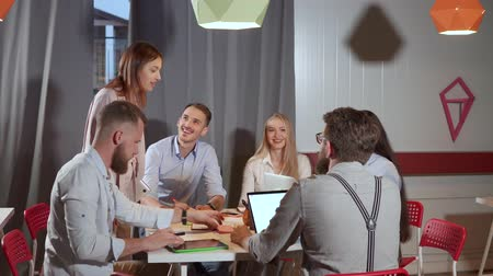 discutir : Young seo specialists are briefing in office. They are sitting at table, woman is approaching, everybody are smiling and laughing
