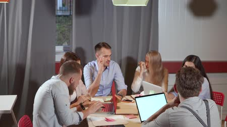 área de trabalho : Male and female office workers are sitting around table and communicating. Managers are chatting and deciding on working meeting