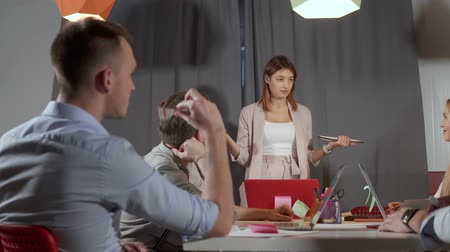 colegas : Brunette woman is performing in front colleagues in briefing time in office. She is answering on questions of female college, two men are discussing Stock Footage