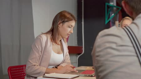 algılayıcı : Young cheerful woman is looking on screen of her working laptop in business meeting. She is scrolling, touching sensor pad and talking with co-workers Stok Video