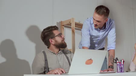 subordinate : Two co-workers men are discussing in working space of office. One man is sitting at table and working with notebook, second is standing near Stock Footage
