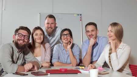 collectief : Friendly office workers are smiling and laughing to camera at office. Young men and women are sitting together in working room Stockvideo