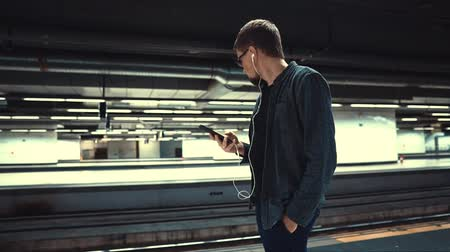 tramwaj : Stylish guy listening to music on smartphone while waiting for train in a subway. Man standing on a platform, music playing in earphones.