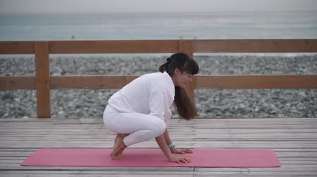 contemplação : Healthy sportswoman doing yoga outdoor by the beach, body relaxation. Changing yoga poses wearing white costume.