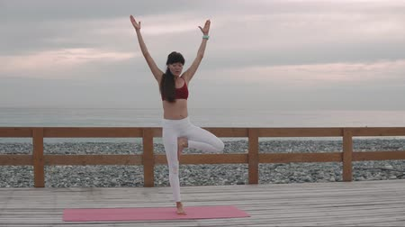 meditál : Sporty brunette is practicing yoga exercise on the beach in the morning. Peaceful young female meditates on a fresh air in yoga pose. Harmony concept.