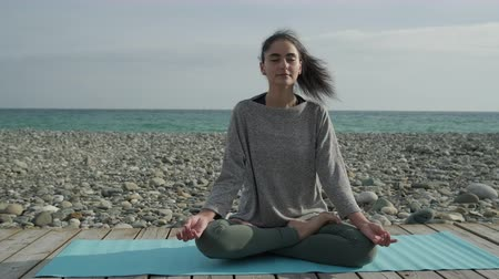 breathing fresh air : Happy woman is practicing yoga lotus asana in morning time in fresh air. She is crossing legs and put hands on them, sitting with closed eyes in sea beach