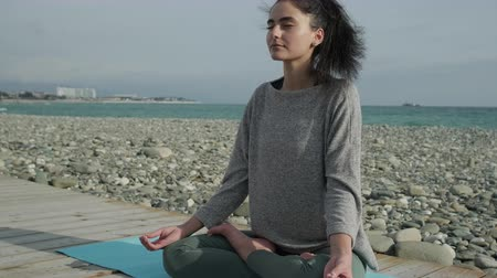 position du lotus : Relaxed girl is making yoga asana in beach area. She is sitting in lotus position with crossed legs and closed eyes Vidéos Libres De Droits